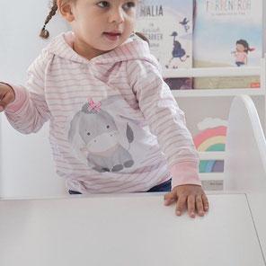 Mädchen mit einem bequemen Hoodie. Der Hoodie ist rosa mit weißen Streifen und hat auf der Vorderseite einen Esel als Bild.