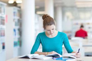 junges mädchen schreibend in bibliothek