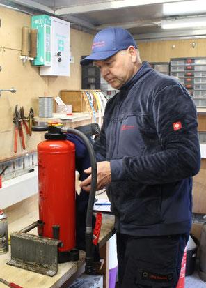 Auf diesem Bild sehen Sie Jörg Baranek bei der Instandsetzung von einem 6 Liter Schaum Feuerlöscher