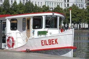 Das weiß gestrichene Alsterboot mit roten Akzenten wartet an der Anlegestelle