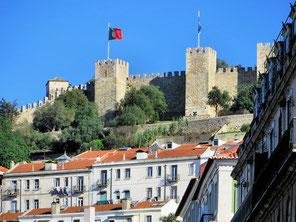 Massive Burgmauern von Sao Jorge mit eckigen Türmen von unten, Häuser darunter