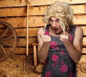 Ein Mann in Frauenkleidern steht in einer Scheune und schaut entsetzt auf seine schmutzigen Fingernägel.