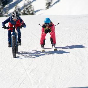 Fetter Spass: Skifahrerin Anita Hendry und ein Fatbiker Gabriel Candinas sind auf der Piste im Skigebiet von Disentis 3000 unterwegs. Foto: Stefan Schwenke