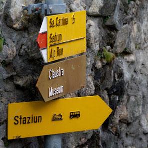Wegweiser in Disentis, Surselva, Graubünden, zeigen die Richtung zum Kloster und zum Museium, zum Bahnhof (Staziun), nach Sedrun und Santa Catarina. Foto: Stefan Schwenke