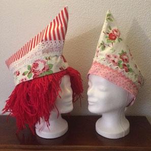 2 Kappen auf Styroporkopf, einmal auf roter Perücke in den Farben rot, rosa und weiß mit Rosenmuster und Streifen