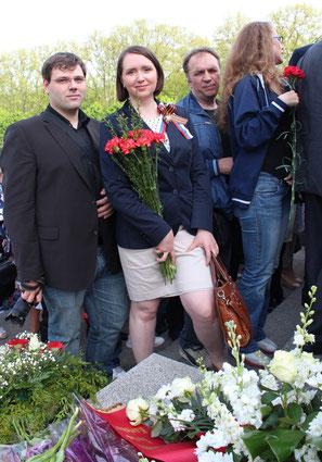 Eine Frau lächelt in die Kamera, mit Roten Nelken, Sankt-Georgs-Band und die Farben Russlands. Wie Tausende gedenken sie der Toten und feiern den Sieg über Hitler-Deutschland. Sowjetisches Ehrenmal Treptow in Berlin am 9. Mai 2015. Foto: Helga Karl