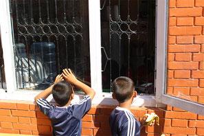 Die Häuser der Hoffnung: Zwei der kleinen Jungs schauen durchs Fenster ins neue Haus