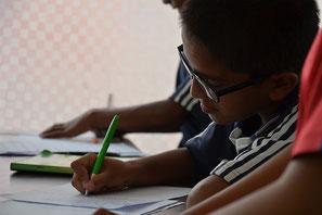 Kind schreibt etwas auf beim machen seiner Hausaufgaben