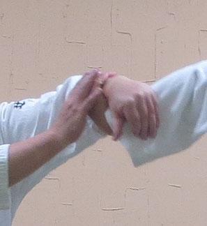 ④小指球も地に向け掌が受けの手首に結ぶ。ここから母指先を地に向けたまま陰の陽に巡って丹田に結ぶ。