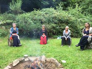 Frauen um das rituelle Feuer auf dem Gelände des Waldhauses inmitten der Natur