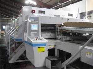 写真:フレキソフォルダーグルアー。別名FFGです。この機械でダンボールが仕上がります。ダンボールに印刷、溝きり、糊貼りをして1枚のダンボールケースを仕上げていきます。オリジナルの印刷、オリジナルの寸法で製造することが可能です。3色(単色)まで印刷できます。