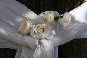 Hochzeitsdekoration mit weißem Tuch und Rosen