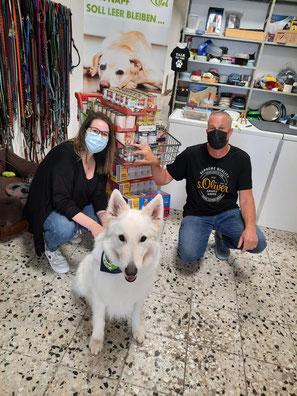 Paar mit Tierfutterspende und weißem Schäferhund