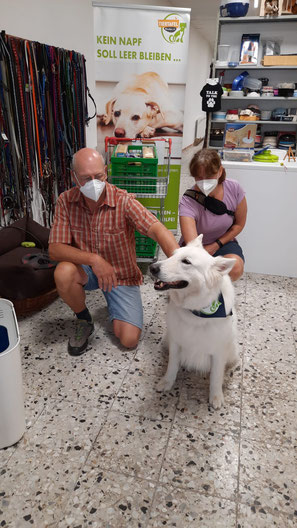 weißer Schäferhund und Übergabe Futterspenden