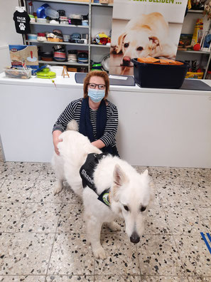 Frau mit weißem Schäferhund und Tierfutter