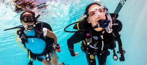 Plongeuse handicapée en piscine assistée par une plongeuse en support