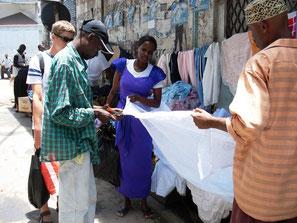 Drei Kenianer bei der Begutachtung von neuen Gardinen in Mombasa