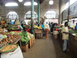 Markthalle in Mombasa mit Gemüseständen, Säcken voller Lebensmittel und Menschen.