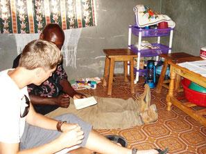 junger Kenianer mit einem weißen Mann in seinem Wohnraum in Mtwapa