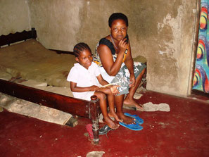 Kenianerin sitzt mit einem kleinen Jungen auf einem Bettgestell in ihrem Schlafzimmer