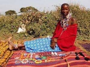 Massai-Frau sitzt auf decke und verkauft Schmuck