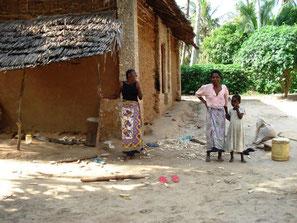 Lehmhütte in kenia mit zwei Frauen und einem Kind und Mais zum trocknen auf Tüchern.