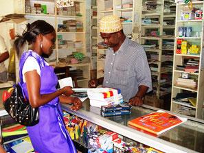 eine Kenianerin im Schreibwarenladen in Mombasa mit einem Verkäufer