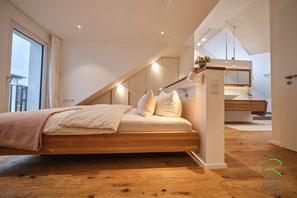 Massivholz Schwebebett auf Gehrung gefertigt im offnen Schlafzimmer mit Badezimmer mit weißem Kleiderschrank in Dachschräge angepasst, Eiche Waschtisch mit Aufsatzbecken u. Spiegelschrank