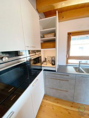 Eckschrank Küchenhochschrank mit Ausziehschrank, Einbauküche in weiß u. Betonoptik mit Eckschrank im Hochschrank zum Ausziehen mit LED-Beleuchtung, Kochinsel in Betonoptik mit Getränkekühlschrank, Versteckte Speisekammer - unauffällig integriert, Küche