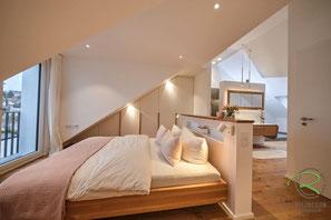 Schwebebett in Eiche massiv u. Dachschrägenschrank in weiß u. Eichengriffleisten, offenes Schlafzimmer u. Badezimmer im Dachgeschoss