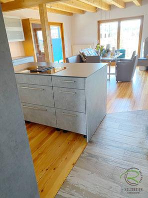 Einbauküche in weiß & Betonoptik mit Kücheninsel u. Muldenlüfter, Küchenhochschrank mit versteckter Speiskammertür, Inselküche in weiß u. Betonoptik mit integrierter Vorratskammertür, offene Wohnraumküche in weiß & Betonoptik