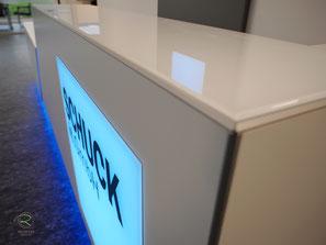 rahmensloses Lichtpanel zur Firmen-Logogestaltung,Verkaufstheke mit flächenbündiges Lichtpanel mit Firmenlogo im Direktdruck, Empfangstheke mit HPL -beschichteter Holzwerkstoff, Empfangsmöbel in weiß mit farbiger, inidrekter LED-BeleuchtungVerkaufstheke