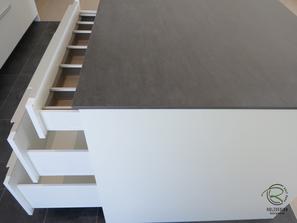 Kücheninsel in weiß mit Keramik-Neolith Arbeitsplatte mit Highboard für Kühl-Gefirrschrank u. Backofen mit brauner, indirekt beleuchteter Nischenrückwand u. Aluminium Griffleiste auf der Front u. flächenbündiger Induktion-Muldenlüfter Siemens