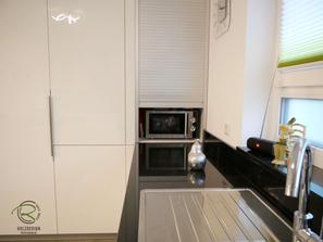 Griffleiste auf Hochglanz-Küchenfront, weiße, offene Hochglanz Wohnküche mit Granit Arbeitsplatte Nero Assoluto poliert mit kleiner Kochinsel u. Sitzplatz, raumhoher Hochschrankzeile mit Glasvitrinen als Küchenabschluss u. Verbindung zum Wohnraum