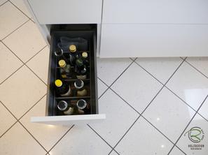 grifflose, weiße Design Küche mit Inneneinteilungssystem Flaschenset von Blum Ambia-Line mit oriongrauen Schubladen von Blum Legrabox mit Halbkochinsel 12 mm Keramik Arbeitsplatte