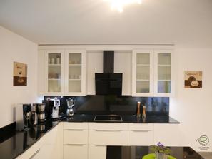 weiße Wohnküche mit Glasoberschränken, Weiße, offene Hochglanz Wohnküche mit Granit Arbeitsplatte Nero Assoluto poliert mit kleiner Kochinsel u. Sitzplatz, raumhoher Hochschrankzeile mit Glasvitrinen als Küchenabschluss u. Verbindung zum Wohnraum