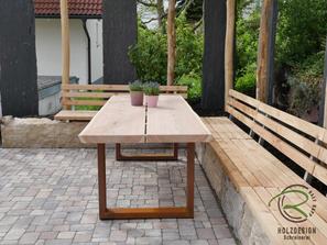 Massiver Gartentisch mit rostigen Metallgestell auf Sitzplatz mit Steinsitzbänken