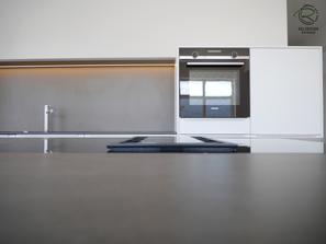 flächenbündiger Einbau von Kochfeldabzug, Kücheninsel in weiß mit Keramik-Neolith Arbeitsplatte mit Highboard für Kühl-Gefirrschrank u. Backofen mit brauner, indirekt beleuchteter Nischenrückwand u. Aluminium Griffleiste auf der Front u. flächenbündiger
