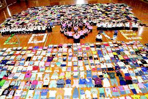 2360着を体育館に並べ、生徒は「LOVE」の文字を作り、支援の意思を込めた=29日、同校体育館