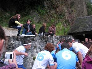 Les rugbymen miment leur match sous les yeux amusés des lavandières.