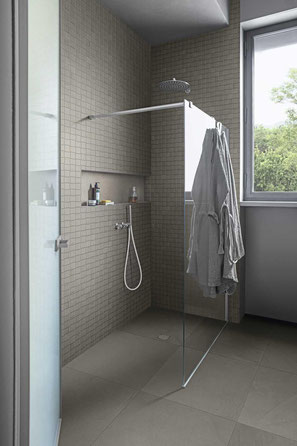 Curbless shower with large gray floor tiles and small, 3D grey wall tiles. There is a glass wall panel with a robe hanging off it on one side.