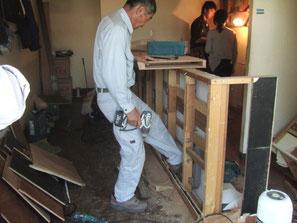 カウンター撤去している後方で電気工事の人と打ち合わせ中の友人の写真