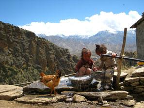Kleine Kinder, die mit Wasser spielen und ein Huhn.
