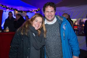 Kundin mit Tobias Volland vor weihnachtlichen Ständen