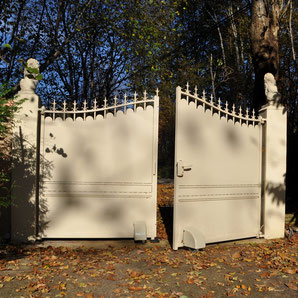 Beige swing gate with AKIA France System wheeled motor drive