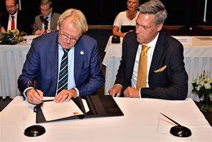 Commissaris van de Koning Jaap Smit zet zijn handtekening, Aart-Jan Moerkerke kijkt toe