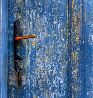 Schlüssel im Schloss einer alten, blauen Holztür