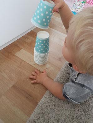 Kleinkind baut einen Turm aus Pappbechern