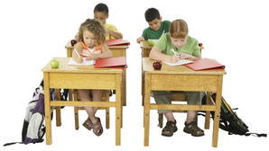 Schüler an Schultischen schreibend
