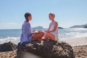 Zwei Frauen meditieren am Strand